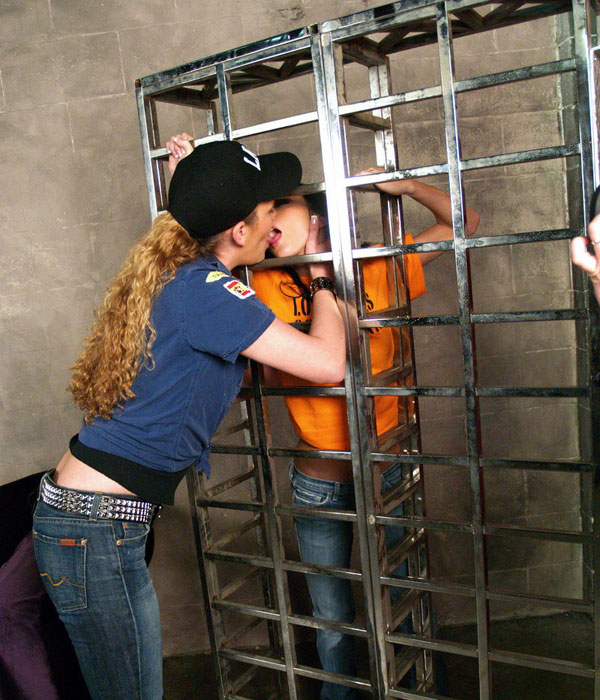 The kissing continues behind the 'bars'